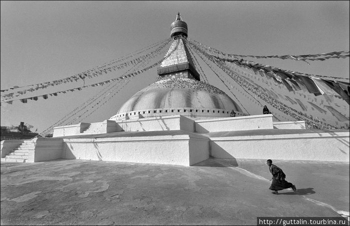 Молодой монах бежит возле ступы Буднатх а Катманду. Непал