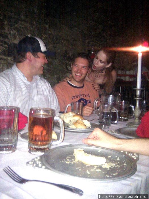 Вампирша пытается отсосать у одного из наших. На столе видны алюминиевые тарелки (возможно, они были оловянные) и бокалы пива, а также закуска — хлеб.