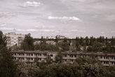 Если бы не пустые глазницы окон и не зловещий силуэт на горизонте, был бы обычный спальный массив старой постройки.