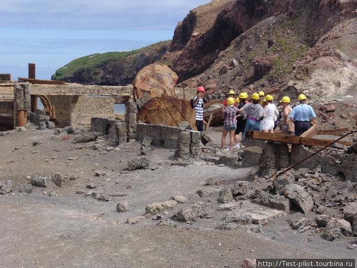 Разрушенный извержением небольшой заводик по производству серы. Каски туристам выдают на случай внезапного извержения — чтобы падающие камни не вышибли мозги