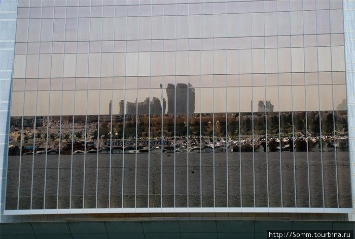 Отражение жизни в стеклянной плоскости дубайского небоскреба.