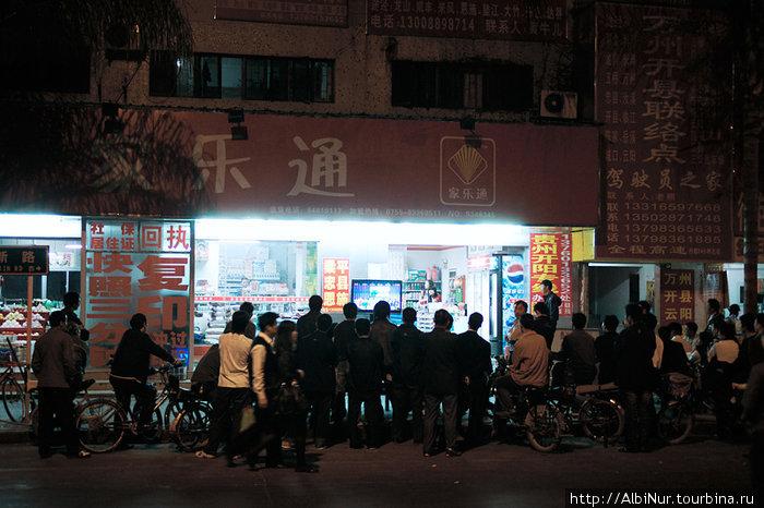 Лонгган — жители городка собрались вечером смотреть ТВ-шоу прямо на улице перед витриной магазина с телевизором. Над этим магазином — наша комната, мы ее сняли в местной общаге для рабочих.