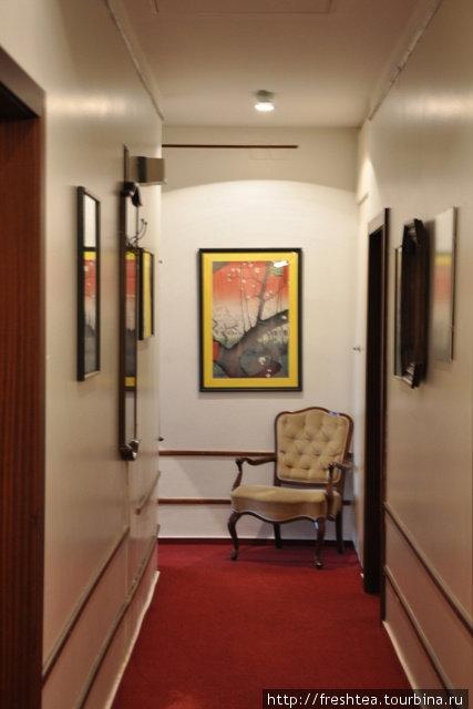 Строгому коридору  добавили шарма репродукции картин и манерное кресло.