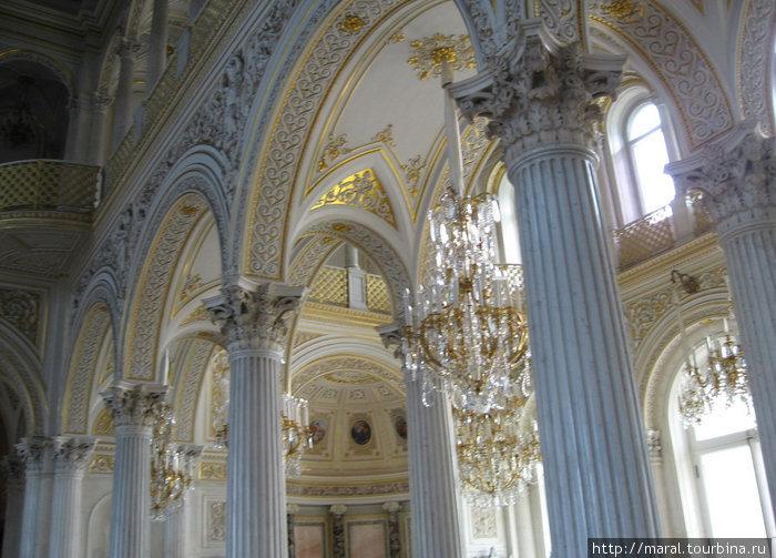 Особую эффектность интерьеру Павильонного зала придают сочетание светлого мрамора с позолотой лепного декора и нарядный блеск хрустальных люстр