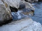 набегающая волна разбивается о камни
