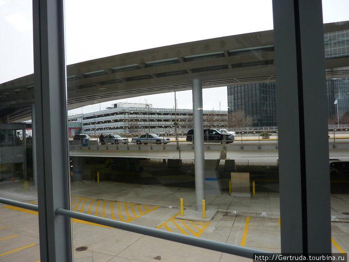 Вид на многоэтажную парковку в аэропорту О'Хара через стекло  окна  терминала.