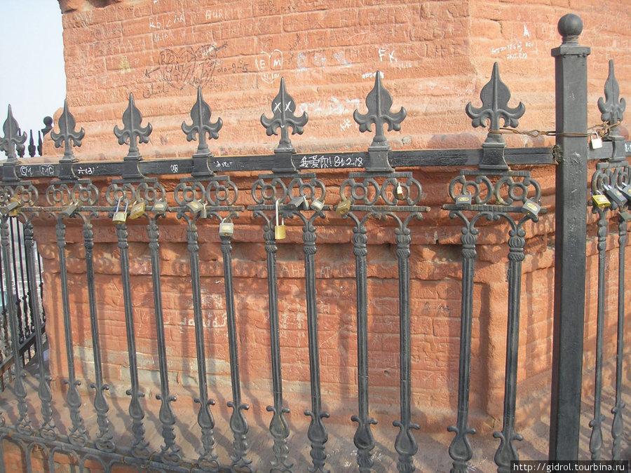 На заборе развешаны замочки, в знак верности и любви, оставленные молодоженами.