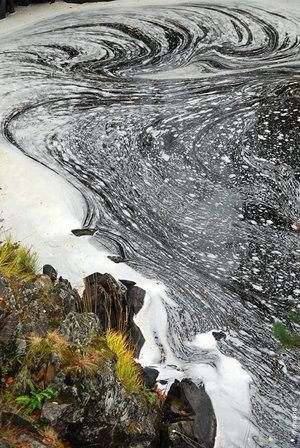 Пена от водопада рисует узоры на воде.
