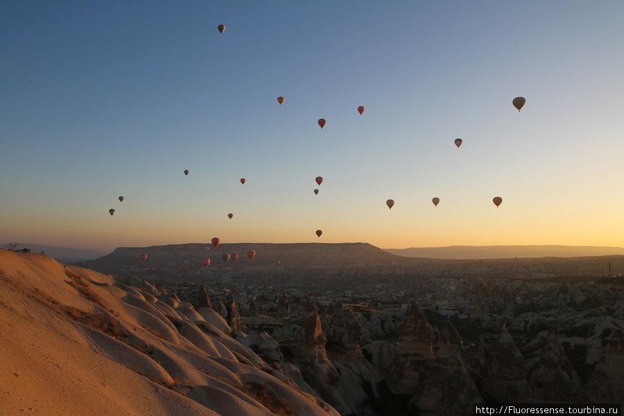 На рассвете десятки разноцветных воздушных шаров устремляются в небо, стремясь застать этот волшебный миг — когда вся долина озарена первыми огненными лучами Солнца.