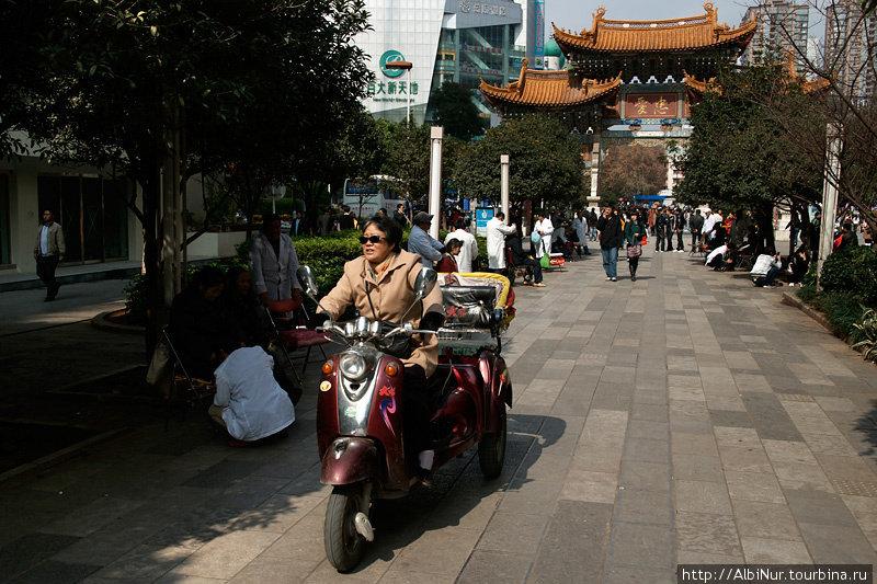 Популярное средство транспорта в Куньмине. На заднем плане, в белых халатах — уличные массажисты. Прямо посреди сквера стоят стулья, мануалы предлагают прохожим свои услуги.
