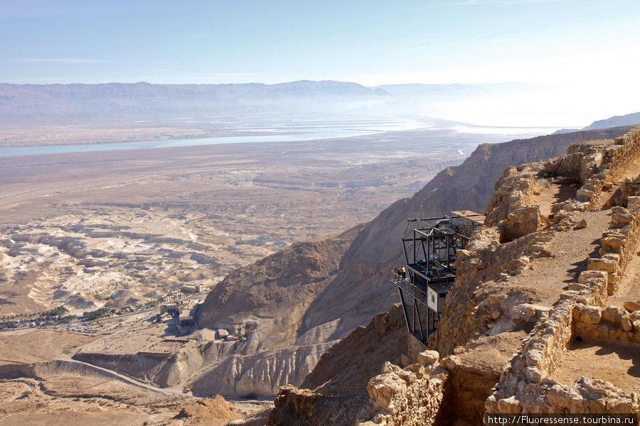 Вид из Масады на юго-восток и канатную дорогу, которая поднимает туристов наверх с берега Мертвого моря. Вделеке видно, что море превращается в реку, прерывается, а потом опять разливается в озеро.