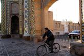 Велосипедист проезжает через ворота Ра Кушк