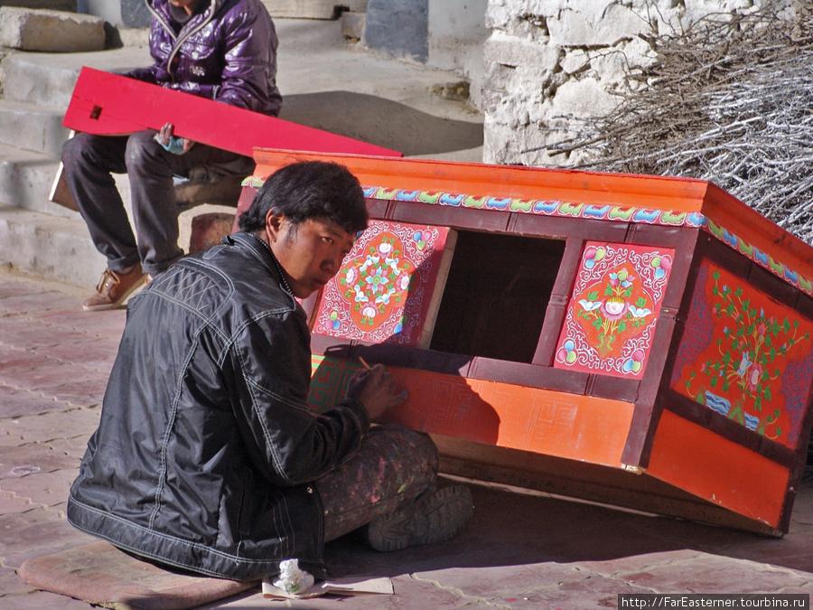Художник расписывает столик чогце прямо на улице, греясь на солнышке