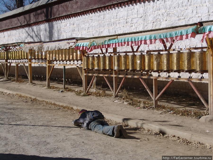 Это не тибетский пьяница, а паломник, совершающий кора вокруг Ташилхунпо