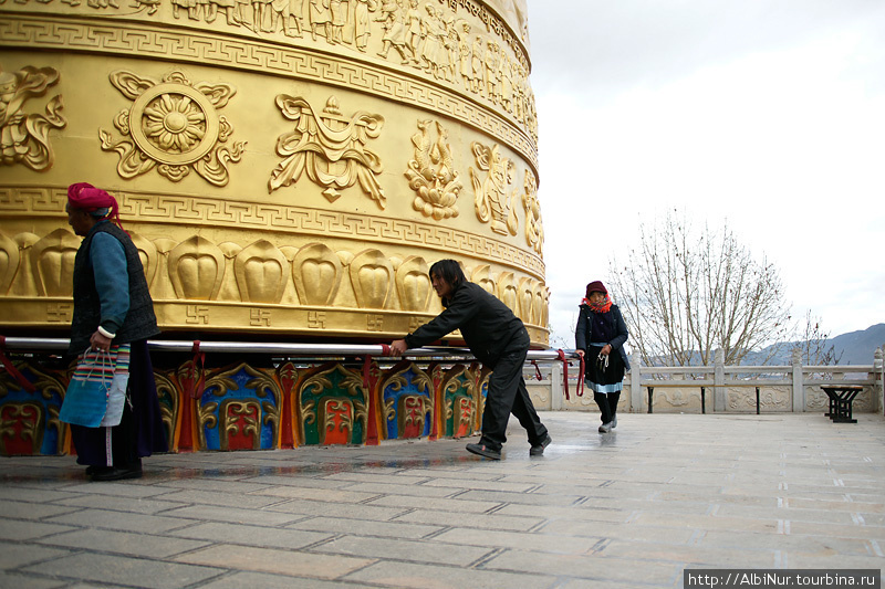 Рядом с храмом на краю города на горе, скрипя вращается огромная тумба. Верующие крутят её кто сколько сможет, чему очень радуются.