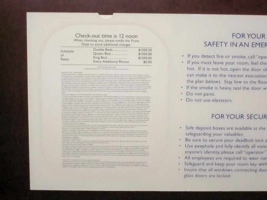 Наклейка на двери изнутри. Написано, что выметаться из номера нужно в 12 часов дня, и стандартная цена за номер 1200 баксов в сутки.